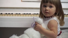 Closeup of a little girl with a toy dog on a background of piano Stock Footage