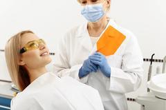 Stomatologist finishing exploration of female mouth Stock Photos