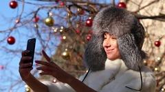 Salfie. Happy young woman in gray fur head cloth outdoor in winter Stock Footage