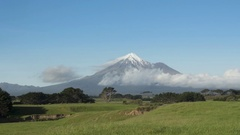 View on volcano Mount Taranaki with snowy top and clouds passing by, New Zealand Stock Footage