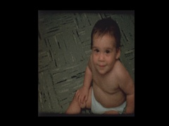 Cute little boy in diapers crawling around plays to camera Stock Footage