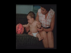 Mother give baby boy in diapers a coaster to play with Stock Footage