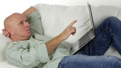 Relaxed Businessman Staying on the Couch in Living and Work Using Laptop. Stock Footage