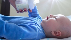 Infant baby crying when get bottle with infant milk from his mothers hands in Stock Footage