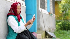 Old woman sits on bench and communicates via tablet computer Stock Footage