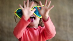 Funny little girl in big glasses looks at camera, shows his hands and tongue Stock Footage