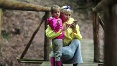 Mother and little daughter looks photos on smartphone Stock Footage