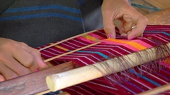 Balinese artist weaves colorful patterns using a traditional, wooden loom Stock Footage