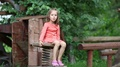 Little girl in red dress sits on a bench HD Footage