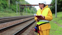 Inspector of railway traffic. Railway worker in yellow uniform with documents Stock Footage