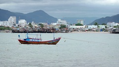 Wooden Fishing Boat Anchored near an Impoverished Community in Vietnam Stock Footage