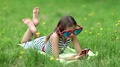 Girl in big glasses lies on grass and communicates via smartphone HD Footage