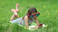 Girl in big glasses lies on grass and communicates via smartphone Stock Footage