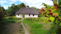 Approaching an Old Fashioned, Thatched Roof Cottage in Ukrainian Village Stock Footage