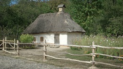 Old fashioned thatched roof cottage in rural, eastern European village Stock Footage