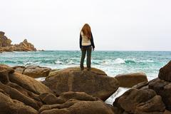 Girl standing on a rock Stock Photos