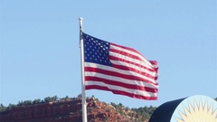 Usa flag waving in front of the sky and the town of Kanab, in Utah, United .. Stock Footage