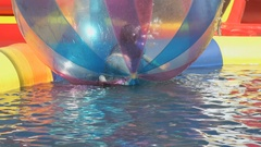 Little boy inside a big inflatable ball in water Stock Footage