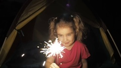 Happy little girl and Bengal fire at night. Stock Footage