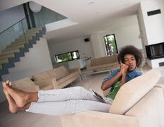 African american woman at home in chair with tablet and head phones Stock Photos