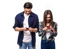 Social network addiction.  Young couple look only in their phone. Stock Photos