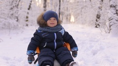 Portrait of laughing little boy in blue overalls on a sled. Stock Footage