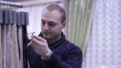 Man choosing the fabric in a textile shop. Stock Footage