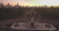 Lumpini Park and Statue at Twilight with Silhouetted Skyscrapers, Aerial Approac Stock Footage