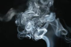 Mystery dense blue smoke over dark background Stock Photos