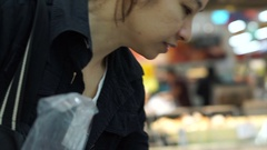 Asian girl shopping in supermarket picking frozen food for home grocery Stock Footage