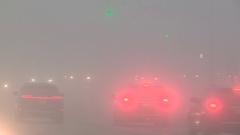 Severe fog with drivers driving in zero visibility in city intersection Stock Footage