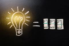 Equal Sign Between Light Bulb And Currency Note Stock Photos