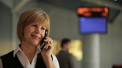Close up shooting of woman talking on phone in departure hall Stock Footage