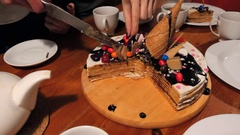 Hands cut by knife delicious big chocolate cake on table Stock Footage