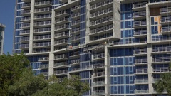 Workmen work on apartment block construction, Sarasota, Florida, USA, zoom in Stock Footage