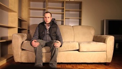 A man stands up and regretfully leaves his couch. Stock Footage