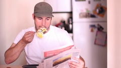A man shoves a whole egg in his mouth while reading the morning paper. Stock Footage