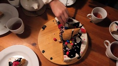 Girl takes cut pieces of cake and puts them onto saucers Stock Footage