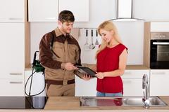 Woman Signing Document In Front Of Male Exterminator Stock Photos