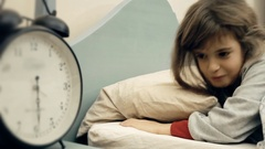 Little girl bed clock nl wake up happy Stock Footage