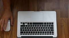 One Hand Typing on a Laptop and the Second Playing Mouse on a Desk. Stock Footage