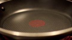 Cracking and egg into a heated frying pan, close-up. Stock Footage