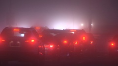 Traffic and heavy fog at night in city intersection Stock Footage