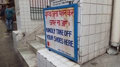 Kindly take off your shoes here sign, entrance to temple, Hindi, India Stock Footage