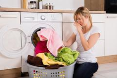 Woman Unloading Smelly Clothes From Washing Machine Stock Photos