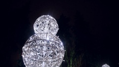 Snowman large glowing balls in the night snowy city Stock Footage