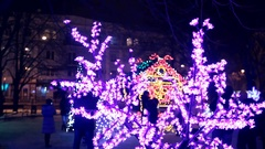 Christmas lights purple color in the night snowy city Stock Footage