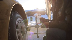 Replacing the wheels with studded tires on a sports car. Snow-covered road Stock Footage