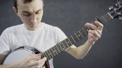 Young guy plays the banjo. Black background Stock Footage