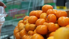 Hand picking orange and put in bag. Fresh fruits selling in supermarket Stock Footage